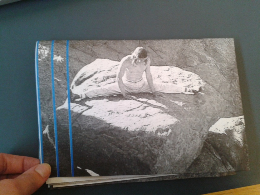 Fatima Hellberg holding a folder poster paper of climber Patrick Edlinger doing the splits on a boulder. Edlinger wears trousers, headband, and is topless. To the left there are three blue vertical lines. The rest of the poster is printed black and white risograph.