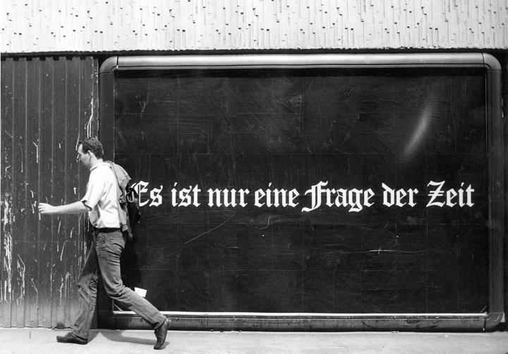 """Black and white photograph of Félix González-Torres' billboard, """"Es ist nur eine Frage der Zeit"""""""
